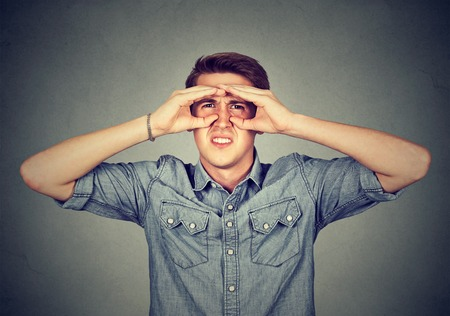 near sighted: Displeased young man looking through fingers like binoculars Stock Photo