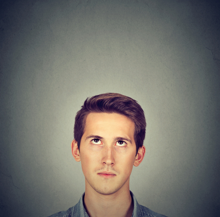 above head: Man looking up gray wall background with blank copy space above head
