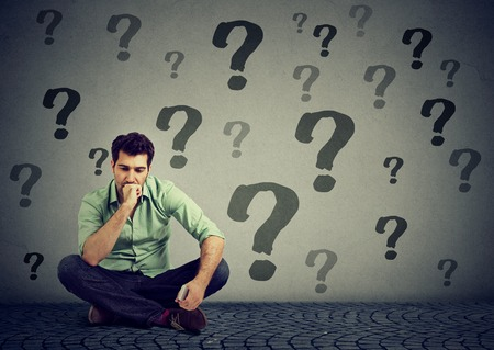 young business man sitting on a floor in front of wall with many questions wondering what to do next. Businessman facing life challenge. Job work problem concept
