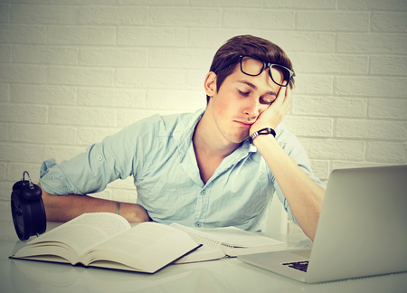 deprivation: Too much work tired sleepy young man sitting at desk with books in front of laptop computer isolated grey brick wall background. Busy schedule in college, workplace, sleep deprivation concept