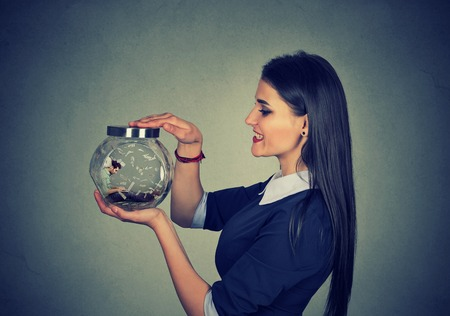 possessive: Woman holding a jar with imprisoned man in it working on laptop under money rain