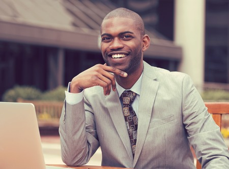 Cheerful business man in a stylish suit sitting at table with laptop outside corporate office block looking at the camera with a happy face expression