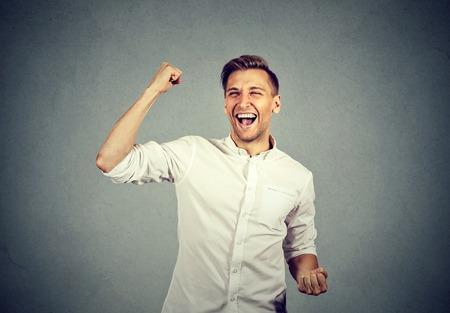 幸せ成功する学生、ビジネスの男が勝利、拳励起祝う分離成功の灰色の壁の背景です。肯定的な人間の感情表情。人生知覚、達成