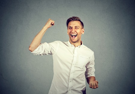 jubilate: Happy successful student, business man winning, fists pumped celebrating success isolated grey wall background. Positive human emotion facial expression. Life perception, achievement