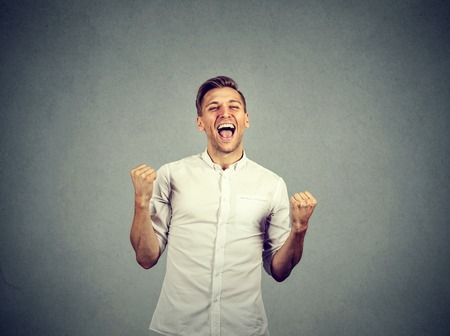 success man: Happy successful student, business man winning, fists pumped celebrating success isolated grey wall background. Positive human emotion facial expression. Life perception, achievement