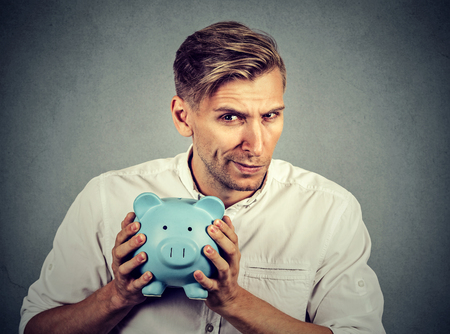 stingy: Young greedy stingy business man holding piggy bank isolated on gray wall background