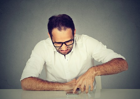 is disgusted: Disgusted man reading a text message scrolling down an email  Stock Photo