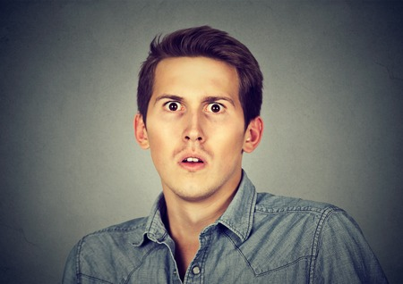 horrifying: Closeup scared frightened young man Stock Photo