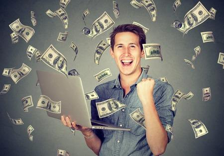 Succesvolle jonge man met behulp van laptop het opbouwen van online business om geld te verdienen dollarbiljetten contant geld te vallen. Regen van het geld. Beginner IT ondernemer succes economieconcept