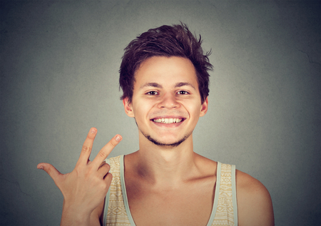 trilogy: man giving a three fingers sign gesture with hand isolated on gray background