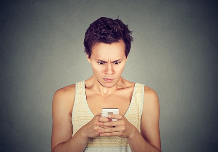 disgusted: Disgusted man reading a text message