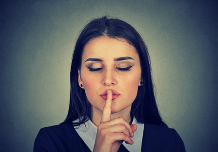 shh: Closeup portrait secretive young woman placing finger on lips asking shh, quiet, silence isolated gray background. Human face expressions, sign emotion feeling body language reaction