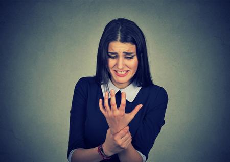 luxacion: mujer joven con su muñeca dolorosa aislado en el fondo de la pared gris. dolor esguince Foto de archivo