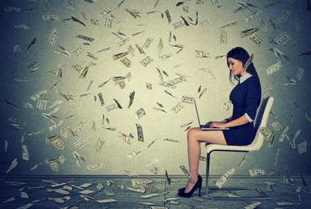 cash money: mujer joven y exitoso uso de un ordenador portátil sentado en una silla la construcción de negocio en línea que hace cuentas de dinero en efectivo en dólares que caen hacia abajo. lluvia de dinero. Principiante empresario de TI concepto de economía éxito