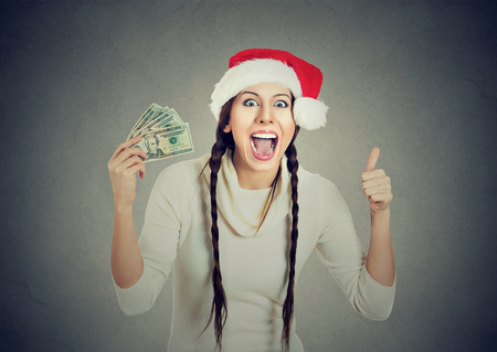 Happy young smiling woman in santa helper red hat with dollar bills showing thumb up, isolated on gray background. Christmas, sale, banking financial concept Stock Photo