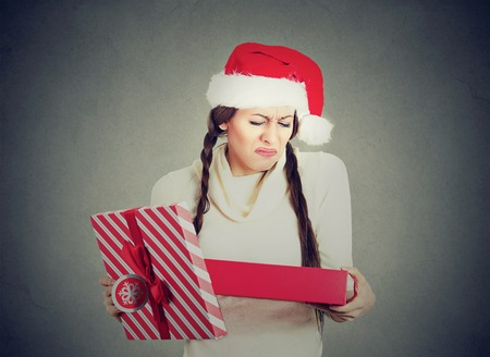 young woman in red santa claus hat opening gift, very upset at what she received, isolated on gray background. Negative human emotion. Holiday shopping concept