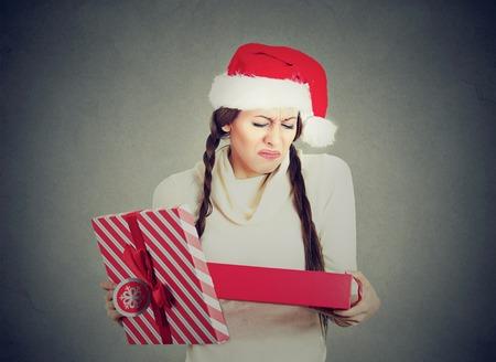 jonge vrouw in de rode hoed van de Kerstman opening gift, erg van streek door wat ze ontvangen, geïsoleerd op grijze achtergrond. Negatieve menselijke emotie. Holiday shopping concept