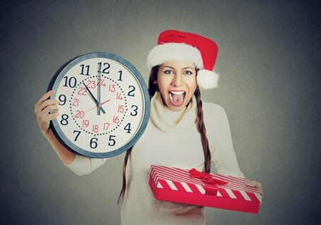 In een haast jonge gelukkige vrouw die rode kerstman hoed houdt klok cadeau doos geïsoleerd grijze achtergrond. Emotie, grappige gezichtsuitdrukking, last minute kerstwinkelen