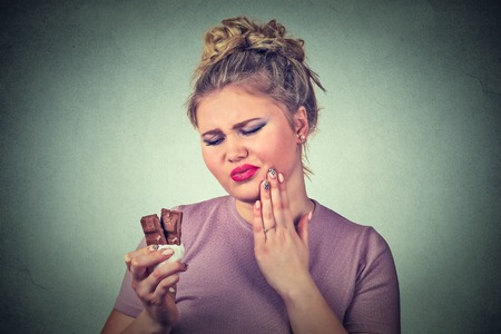 sweet tooth: chocolate lover young woman with toothache sensitive teeth