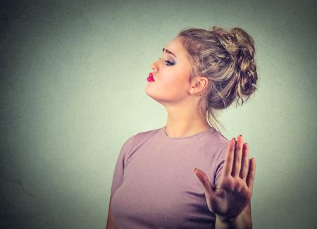 Mujer joven molesto estirado enojado con mala actitud dando a hablar con gesto de la mano con la palma hacia afuera aislado fondo de la pared gris. cara emoción negativa lenguaje corporal sensación expresión humana Foto de archivo - 67314705