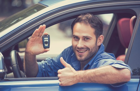 new car: Happy, smiling, young man sitting in his new blue car showing keys thumbs up isolated outside dealership lot. Personal transportation purchase concept Stock Photo