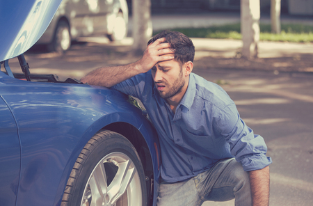 Man with broken down car flat tire in the middle of the street Standard-Bild