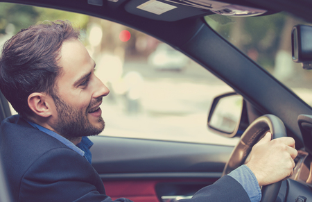 new car: Happy man with hands on wheel driving new car  Stock Photo