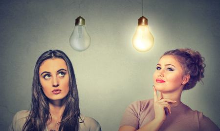 Two women thinking looking up at light bulbs isolated on grey wall background. Human face expressions, emotions, perception. Cognitive skills ability concept Stock Photo