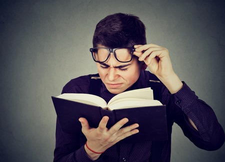 Closeup young man with eye glasses trying to read book, having difficulties seeing text, has sight problems. Eyesight issues concept. Human face expression