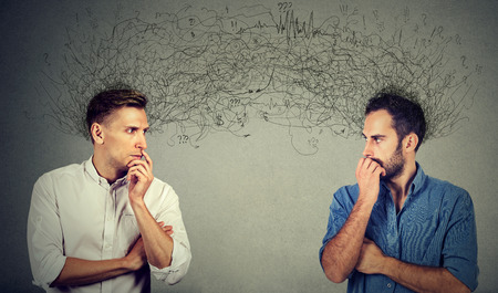 Side profile of two preoccupied businessmen looking at each other exchanging with many thoughts