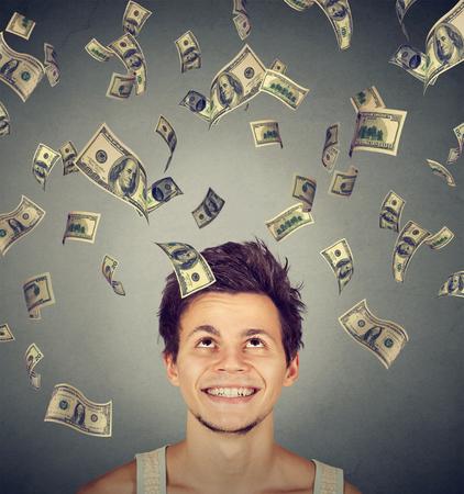 cash money: Hombre feliz bajo la lluvia de dinero cayendo billetes de un dólar billetes de banco. concepto de la libertad financiera