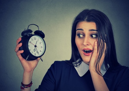 perfectionist: Anxious young woman looking at alarm clock. Time pressure concept. Human emotions face expression