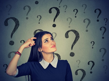 Portrait confused thinking young woman bewildered scratching head seeks a solution looking up at many question marks isolated on gray wall background. Human face expression Banque d'images