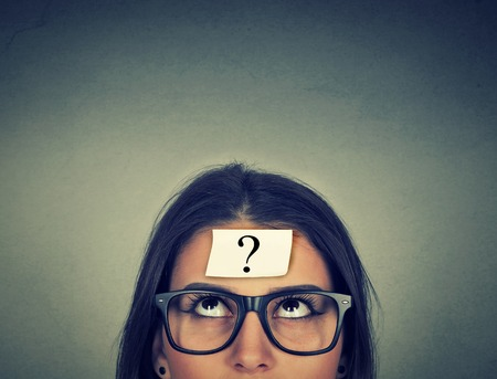 in thought: thinking woman with question mark on gray wall background