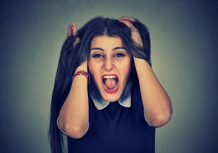 pulling hair: Stressed out young woman pulling her hair  Stock Photo