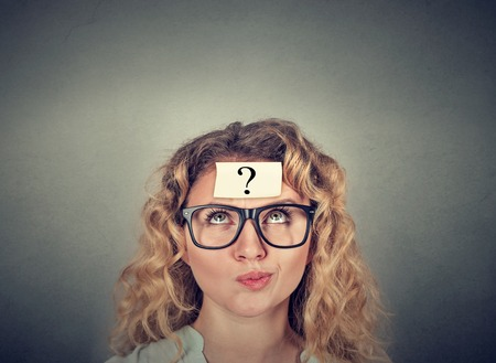 thinking confused woman with question mark on gray wall background Standard-Bild