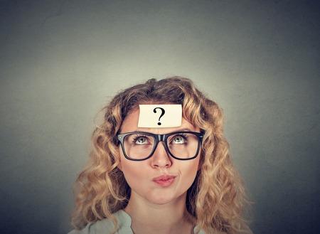 Pensamiento de la mujer confundida con signo de interrogación sobre fondo gris de la pared Foto de archivo - 67332679