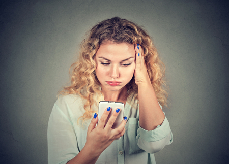 miffed: annoyed young woman, pissed off by what she saw on her cell phone isolated on gray background