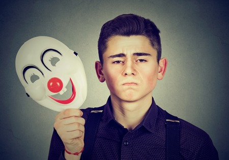 simulate: Young sad man taking off happy clown mask isolated on gray wall background. Human emotions. Split personality concept Stock Photo
