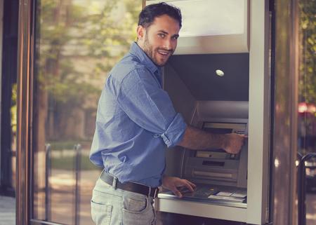 Jong gelukkig man met behulp van ATM