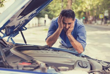 jonge gestresste man problemen met zijn kapotte auto kijken in frustratie op mislukte motor