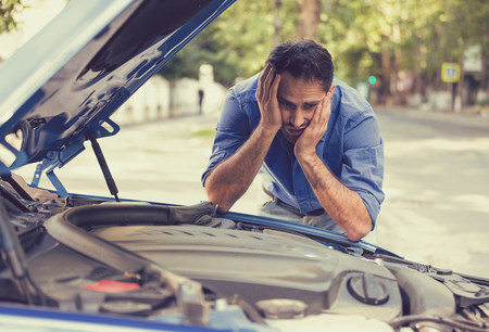 car trouble: young stressed man having trouble with his broken car looking in frustration at failed engine