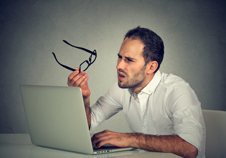 business problems: Closeup portrait business man with glasses having eyesight problems confused with laptop isolated on gray background. Vision related changes. Human face expression