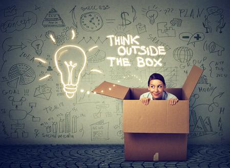 Pensate al di fuori del concetto di scatola. La giovane donna che esce dalla scatola isolata su informazioni grigio muro di grafica di sfondo
