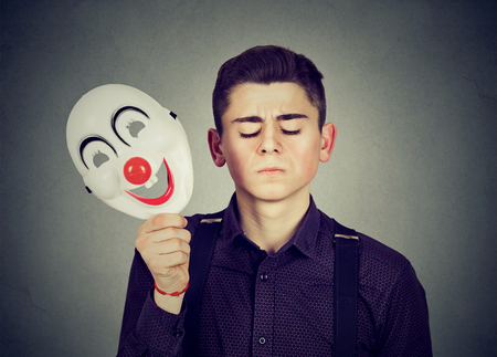 likable: Young sad man taking off happy clown mask isolated on gray wall background. Human emotions. Split personality concept Stock Photo
