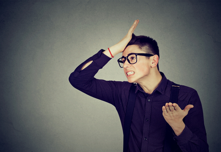 Regrets wrong doing. Silly young man, slapping hand on head having duh moment isolated on gray background. Human emotion facial expression feelings and body language Stock Photo - 68412831