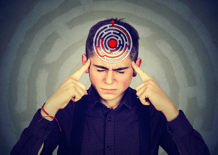 recollection: Problem solution concept. Young stressed man solving puzzle isolated on gray background