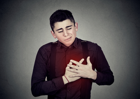 excruciating: Adult man suffering from severe sharp heartache, chest pain. Heart disease concept Stock Photo
