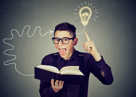 Amazed young man in glasses reading book comes up with an idea