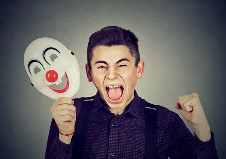 Portrait upset angry screaming man holding clown mask expressing cheerfulness happiness isolated on gray wall background. Human emotions feelings Foto de archivo